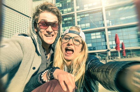 student travel: Young hipster couple in love taking a funny selfie in urban city background - Alternative concept of fun and interaction with new trends and technology - Vintage filtered look with blurred edges