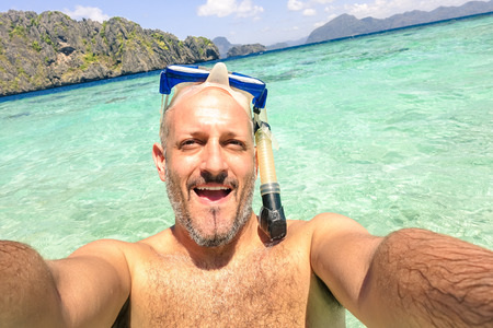 pigeon holes: Handsome man taking a selfie during islands hopping at El Nido in Palawan - Boat trip snorkeling in exotic scenarios - Adventure travel lifestyle around Philippines - Composition with tilted horizon