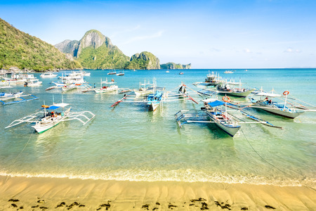 hopping: Front beach with longtail boats in El Nido - Beautiful tropical destination in Palawan Philippines - Travel concept in exclusive locations in south east asia - Nature wander trip around the world Stock Photo