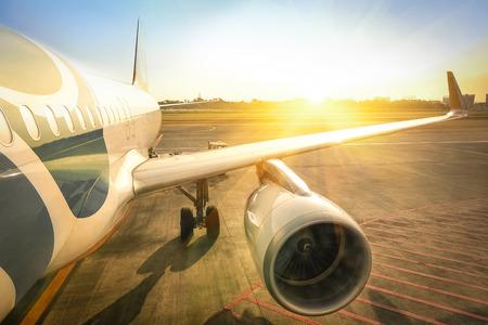 Vliegtuig bij terminal gate klaar voor start - Moderne internationale luchthaven tijdens zonsondergang - Begrip emotionele reis en dwalen rond de wereld - pictogram op vliegtuigen lichaam is sterk gewijzigd Stockfoto