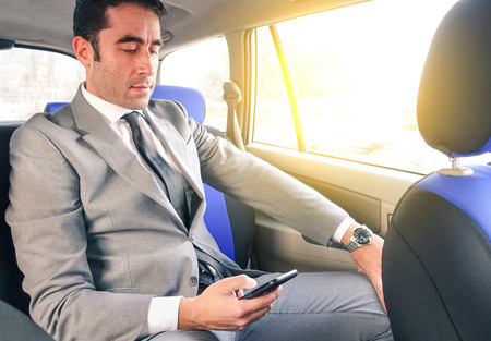 sms: Young handsome businessman sitting in taxi cab while texting sms with smartphone - Business concept with modern man using smart phone - Soft vintage editing with artificial sunlight from the window Stock Photo