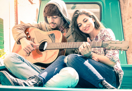novio: Pares rom�nticos de los amantes tocando la guitarra en el mini coche anticuado - Nostalgic concepto retro del amor con el foco suave en las caras de novio y novia - filtro vendimia desaturado Sobreexpuesta