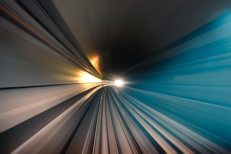 zoom in: Subway tunnel with blurred light tracks in the gallery - Concept of modern metro underground transport and connection - Radial zoom motion blur due to the speed of the train