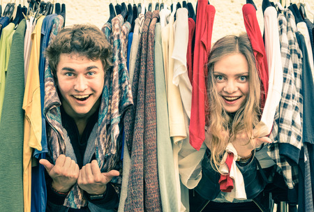 lovers: Young hipster couple in love at the weekly cloth market - Best friends sharing free time having fun and shopping in the old town - Lovers enjoying everyday life moments on a vintage filtered look