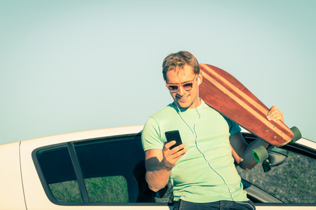 modern lifestyle: Young hipster man with smartphone listening music during trip break next his car - Concept of new trends and modern technologies mixed with a retro lifestyle - Soft desaturated vintage filtered look
