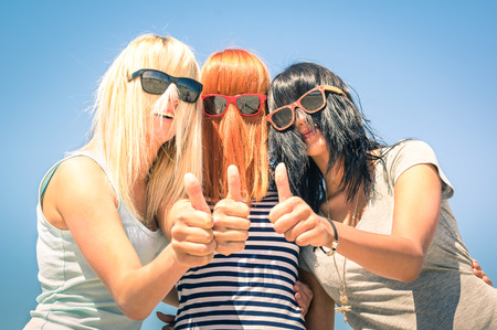 Group of young girlfriends with focus on colored funny hair and sunglasses - Concept of friendship and fun in the summer expressing positivity with thumbs up - Best friends sharing happiness together