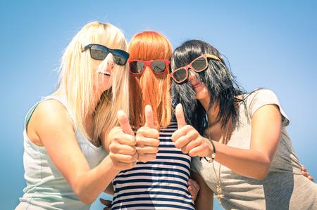 anteojos de sol: Grupo de amigas jóvenes con enfoque en color el pelo divertido y gafas de sol - concepto de la amistad y la diversión en el verano que expresa la positividad con los pulgares arriba - Mejores amigos compartiendo la felicidad juntos