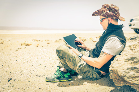Young hipster man sitting in desert road - Concept of modern technologies with a alternative travel lifestyle - Overexposed vintage desaturated filtered look with focus on the hand using the laptop