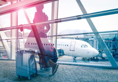 voyage: concept de Voyage avec femme et valise en mouvement rapide à la porte de terminal de l'aéroport - Double exposition regarder avec un accent sur l'avion en arrière-plan - Violet marsala soleil fusée avec vintage filtrée édition