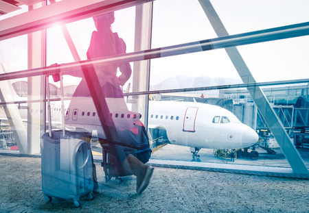 arrivals: Travel concept with woman and suitcase moving fast to airport terminal gate - Double exposure look with focus on the aircraft in the background - Violet marsala sun flare with vintage filtered editing