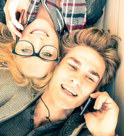 amistad: Pareja en el amor que se divierten con los tel�fonos inteligentes - Cierre de los amantes inconformista felices - Concepto de la juventud con las nuevas tendencias y tecnolog�as - Warm mirada filtrada vendimia saturada inspirar la pr�xima primavera