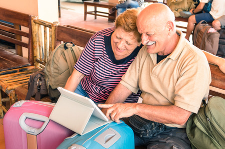 happy old people: Happy senior couple sitting with digital laptop and travel baggage during adventure trip around the world - Concept of active elderly lifestyle and interaction with new trends and technologies