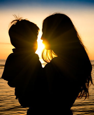 Mother and son in a deep moment of love during sunset at beach - Concept of union and tender connection between a young mama and his lovely child - Modified shape of silhouettes with filter sun flare