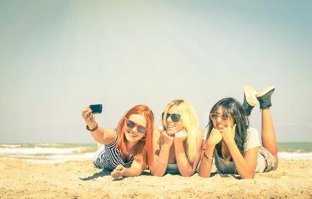with friends: Novias felices que toman una Autofoto en la playa - concepto de la amistad y la diversi�n en el verano con las nuevas tendencias y la tecnolog�a - Mejores amigos disfrutando de momentos con tel�fono inteligente moderno - mirada filtrada Vintage Foto de archivo