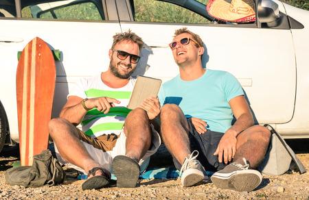 amicizia: Giovane vita bassa migliori amici per divertirsi con tavoletta in un momento viaggio in auto - concetto di moderne tecnologie e nuove tendenze durante le vacanze di viaggi alternativi sulla strada - Soft epoca filtrata sguardo