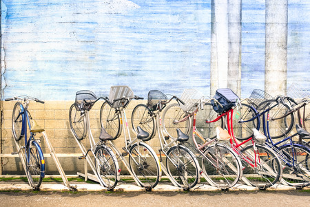 a two wheeled vehicle: Multicolored vintage bicycles in metal rack in Tokyo city