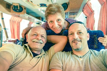 senior friends: Senior happy couple with son taking a selfie during a bus trip in Laos - Adventure travel in south east asia - Concept of active elderly and love sharing moments with family - Vintage filtered look