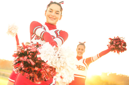 pom: Group of cheerleaders performing outdoors  - Concept of cheerleading team sport training at high school during sunset - Tilted horizon composition and warm filter with sun backlighting