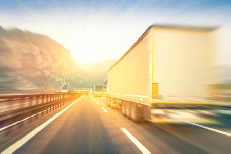 Generiska semi lastbilar fortkörning på motorvägen vid solnedgången - Transport branschbegreppet med semitruck behållare kör till bergspass - Varm redigering med pop filtrerad solsken och suddiga kanter