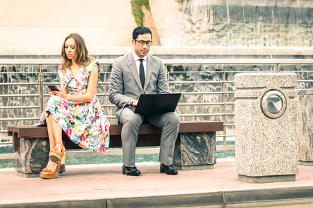 Couple in moment of disinterest  - Break up concept and new technologies addiction - Business man at laptop ignoring girlfriend texting sms with smartphone - Neutral color tone due to the cloudy day photo