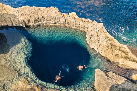 Deep blue hole at the world famous Azure Window in Gozo island - Mediterranean nature wonder in the beautiful Malta - Unrecognizable touristic scuba divers swimming to adventure water cave 스톡 콘텐츠