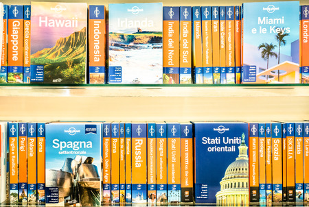 RIMINI, ITALY - MARCH 15, 2014: Lonely Planet volumes on a shelf. The famous company is the largest travel guide book publisher in the world and is owned by the american billionaire Brad Kelley 新聞圖片