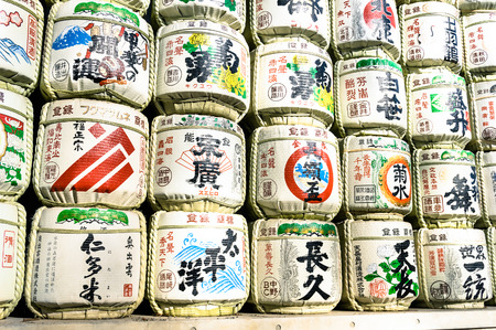 near beer: TOKYO - MARCH 2, 2015: barrels of sake wrapped in straw in Yoyogi Park near Meiji Shrine. The alcoholic beverage of Japanese origins made from fermented rice has a brewing process similar to beer.
