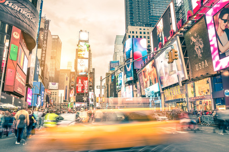 NEW YORK - DECEMBER 22, 2014: blurred yellow taxi cab and rush hour congestion at Times Square in Manhattan, one of the most visited tourist attractions in the world. Warm vintage filtered editing.