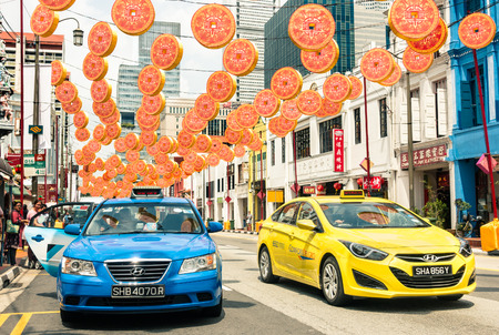 a yellow taxi: SINGAPORE - FEBRUARY 12, 2015: multicolored taxi cabs driving on South Bridge Road near the corner with Temple Street in Chinatown district with colorful decorations for the upcoming Chinese New Year