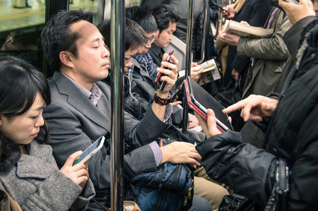 smartphone addiction: TOKYO -MARCH 2, 2015: people busy with smartphones and tablets in the underground train. The combination of  the subway network of the Tokyo and Toei metros, comprises 290 stations and 13 lines.