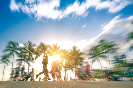 Man running through the crowd at sunset on Kalakawa Ave - Front walk promenade of Waikiki Beach in Honolulu Hawaii - Freedom and wander concept - Radial zoom defocusing with warm vintage filtered look