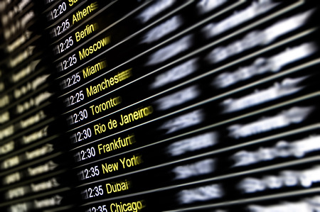 world travel: Blurred defocused digital display at international airport with flight connections and cities around the world - Concept of travel lifestyle with exclusive destinations worldwide - Departure and arrivals terminal gates Stock Photo