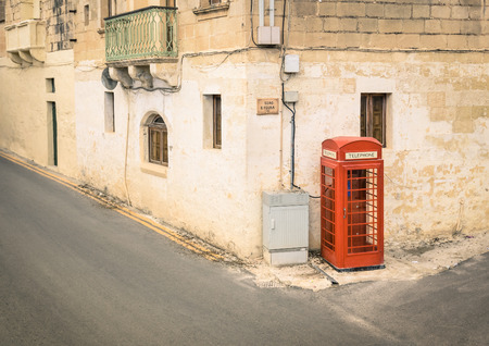 Red telephone cabin in the medieval old town of Victoria in Gozo - Mediterranean archipelago of Malta Stock Photo