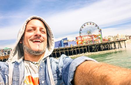 america: Handsome man taking a selfie at Santa Monica Pier with ferris wheel  Stock Photo