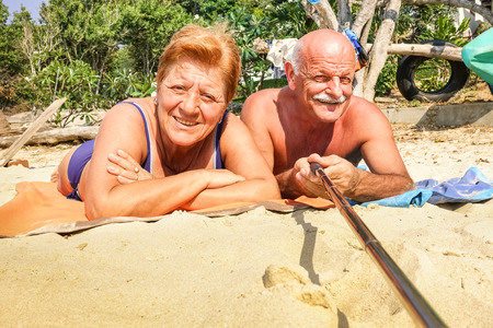 Senior happy couple taking selfie with stick in Thailand trip  photo