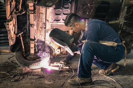 Young man mechanic worker repairing old vintage car body in messy garage  스톡 콘텐츠