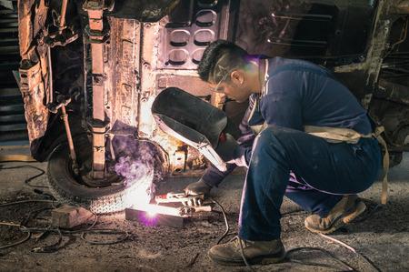 Jonge man mechanic werknemer repareren van oude vintage auto lichaam in rommelige garage Stockfoto