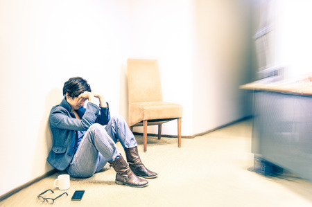 depressed girl: Depressed hipster business woman sitting on the floor with headache  Stock Photo