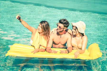 Best friends taking selfie at swimming pool with yellow airbed