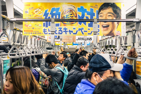 TOKYO - FEBRUARY 26, 2015: full train during rush hour in the underground. The combined subway network of the Tokyo and Toei metros counts 290 stations and 13 lines. Crowded cropped composition . Редакционное