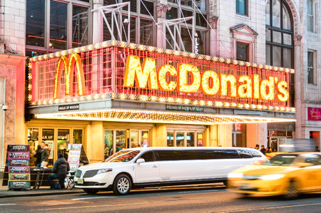 42nd: NEW YORK - MARCH 25, 2015: illuminated neon sign of burger chain McDonalds along 42nd street with parked limousine and speeding blurred taxi in Times Square, one of the world most visited attractions.