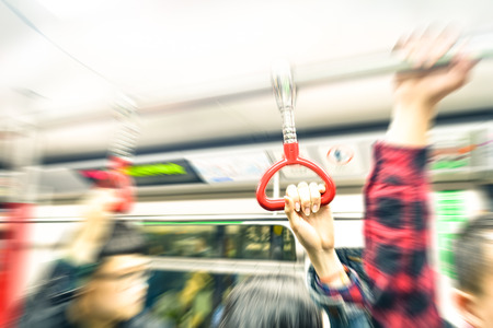 handle bars: Concept of metropolitan transportation during rush hour - Hong Kong underground with radial zoom defocusing and vintage filtered look - Focus on the hand holding train handle during subway trip