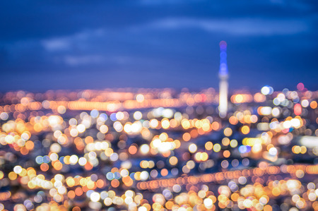 aerial: Bokeh of Auckland skyline from Mount Eden after sunset during the blue hour - New Zealand modern city with spectacular nightscape panorama - Blurred defocused night lights Stock Photo