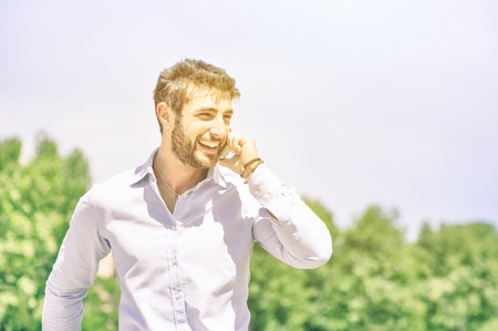 Happy young business man at park with smartphone having a break after a working day - Modern concept of nature mixed with human urban and metropolitan lifestyle - Overexposed vintage filtered look