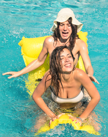 pool fun: Best friends in bikini enjoying time together outdoors in swimming pool - Concept of freedom and happiness with two girlfriends having fun in the summer