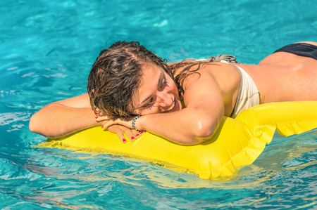 matress: Beautiful young woman relaxing on a yellow inflatable mattress in clear blue water - Summer chilling out with girl in swimming pool at exclusive hotel resort Stock Photo