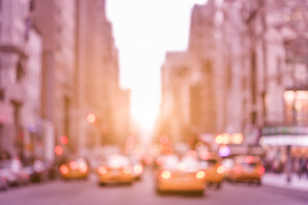 avenues: Rush hour with defocused yellow taxi cabs and traffic jam on 5th avenue in Manhattan downtown at sunset - Blurred bokeh postcard of New York City on a vintage marsala color filtered look