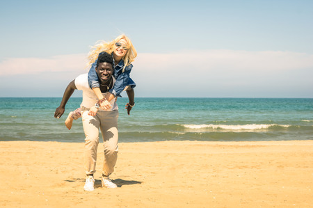 multi race: Young multiracial couple at the beach having fun with piggyback jump - Happy mixed race boyfriend and girlfriend playing at the beginning of love story - Multi ethnic integration love against racism Stock Photo