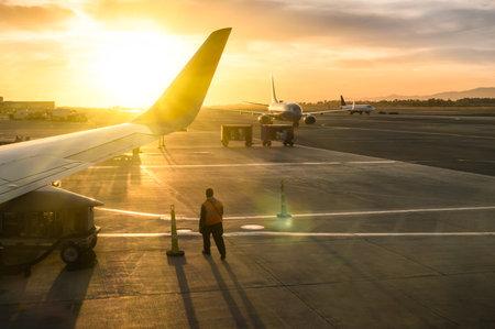 日没 - 世界中の感情的な旅行の概念 - ソフト フォーカスと太陽レンズ フレア バックライトのために国際空港のターミナルのゲートで飛行機の翼の