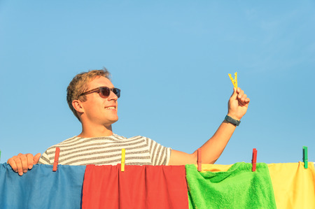 laundry concept: Young handsome hipster man hanging colorful laundry with clothespin - Concept of single lifestyle taking care on houseworks - Funny guy hanging multicolored clothes on bright sunny day outdoors